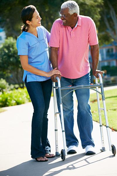 Carer Helping Senior Man With Walking Frame